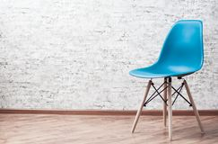 Modern blue plastic chair in an empty room with wooden floor on gray Brick Wall Background. With copy space royalty free stock photography