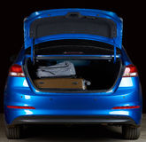 Modern blue sedan trunk. Full with luggage bags isolated on black background Stock Images