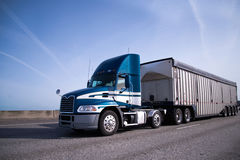 Modern blue semi truck with day cab and bulk trailer on interstate highway. Contemporary big rig blue semi truck with high day cab and covered semi trailer for royalty free stock image