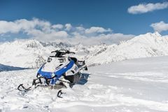Modern blue snow vehicle on the background of snow mountains. Modern blue snow vehicle against the scenic background of high snow mountains peaks and cloudy sky royalty free stock photos