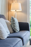 Modern blue sofa with pillows and lamp in living room Royalty Free Stock Image