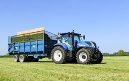 Modern blue tractor pulling a trailer in grass field Stock Images