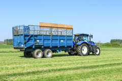 Modern blue tractor pulling a trailer in grass field Stock Image