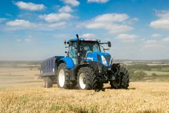 Modern blue tractor pulling a trailer in harvest field. Modern blue new holland tractor pulling blue trailer with crops in stubble field and big sky Royalty Free Stock Images