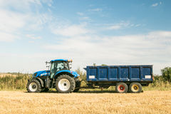 Modern blue tractor pulling a trailer in harvest field. Modern blue new holland tractor pulling blue trailer with crops in stubble field and big sky Royalty Free Stock Photos