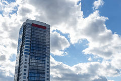 Modern blue and white stone condo tower on blue sky in the background Stock Photos