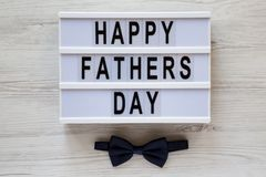 Modern board with `Happy Fathers Day` words over white wooden surface, top view. Overhead, from above, flat lay. Father`s day stock image