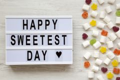 Modern board with `Happy Sweetest Day` word and candy on a white wooden background, overhead view. Top view, flat lay, from abov. E royalty free stock photo