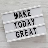 Modern board with `Make today great` words on a white wooden table, top view. Overhead, from above. Flat lay stock photo