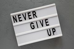 Modern board with `Never give up` words over concrete background. Flat lay, from above, overhead. Close-up royalty free stock photography