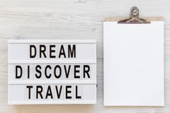 Modern board with text `Dream Discover Travel` and clipboard on white wooden table, top view. From above, flat lay, overhead. Space for text royalty free stock photos