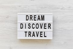 Modern board with text `Dream Discover Travel` word over white wooden background, top view. From above, flat lay. Overhead Stock Photography