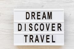 Modern board with text `Dream Discover Travel` word over white wooden surface, top view. From above, flat lay. Overhead Royalty Free Stock Images