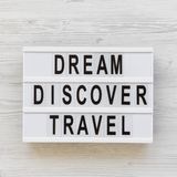 Modern board with text `Dream Discover Travel` word over white wooden surface, top view. From above, flat lay. Overhead stock photography