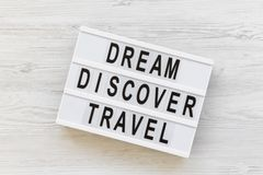 Modern board with text `Dream Discover Travel` word on white wooden background, top view. From above, flat lay. Overhead Stock Photos