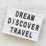 Modern board with text `Dream Discover Travel` word on white wooden background, top view. From above, flat lay. Overhead royalty free stock photography
