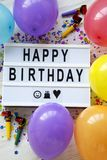 Modern board with text `Happy Birthday`, decoration party on white wooden background, overhead view. Flat lay, top view, from ab stock photo