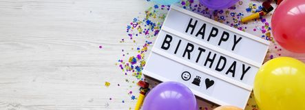 Modern board with text `Happy Birthday`, decoration party on white wooden surface, top view. Flat lay, overhead, from above. royalty free stock images