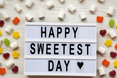 Modern board with text `Happy Sweetest Day` word and candy over white wooden background, overhead view. From above, flat lay. Top view stock photography