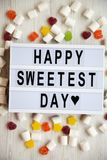 Modern board with text `Happy Sweetest Day` word and candy over white wooden background, top view. From above, flat lay, overhea. D royalty free stock image