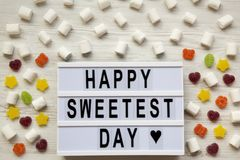 Modern board with text `Happy Sweetest Day` word and candy over white wooden surface, top view. From above, flat lay stock photo