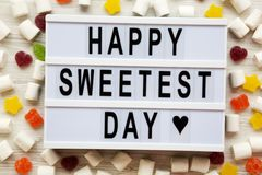 Modern board with text `Happy Sweetest Day` word and candy over white wooden surface, top view. From above, flat lay. Overhead royalty free stock photos