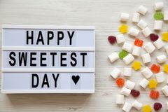 Modern board with text `Happy Sweetest Day` word and candy over white wooden surface, view from above. Top view, flat lay, overh. Ead stock photos