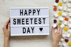 Modern board with text `Happy Sweetest Day` word and female hands with candy over white wooden background, top view. From above,. Flat lay, overhead royalty free stock images