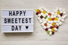 Modern board with text `Happy Sweetest Day` word and heart made of candies over white wooden background, top view. From above, f. Lat lay, overhead stock photos