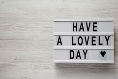 Modern board with text `Have a lovely day` on a white wooden background, top view. From above, flat lay, top view. Copy space.  royalty free stock photo