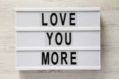 Modern board with text `Love you more` on a white wooden surface, top view. Flat lay, overhead, from above stock photo