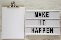 Modern board with text `Make it happen`, clipboard on a white wooden surface, top view. From above, flat lay, overhead. Space fo royalty free stock photos