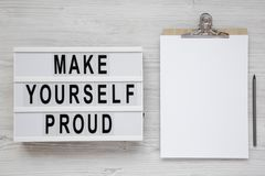 Modern board with text `Make yourself proud` on a white wooden surface, top view. Flat lay, overhead, from above. Copy space stock photos
