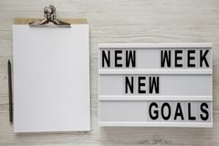 Modern board with text `New week new goals`, pencil and noticepad over white wooden background, top view. From above, flat lay, stock photography