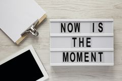 Modern board with text `Now is the moment`, tablet with blank screen, noticepad on a white wooden background, overhead view. Fro. M above, flat lay stock photo