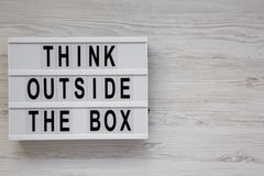 Modern board with `Think outside the box` words on a white wooden background, top view. Flat lay, overhead, from above. Copy spa stock image