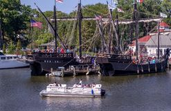 Modern boat and Columbus ships Nina and Pinta. September 3, 2017 South Haven MI USA; A modern Pontoon boat floats by the replica Columbus ships the Nina and the Stock Photos