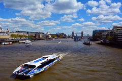 Modern boat on River Thames and Tower Bridge and HMS Belfast in the background, London, United Kingdom Royalty Free Stock Image