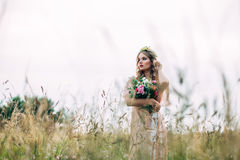 Modern Boho Fashion Bride. Girl in elegant dress holding a bunch of flowers Stock Images