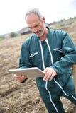 Modern bonde som använder minnestavlan i fält arkivfoton