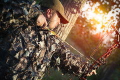 Modern Bow Hunter. Hunter with a bow and arrow hunting in the forest Stock Photos