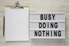 Modern box with text `Busy doing nothing`, noticepad and pencil on a white wooden background, top view. From above, flat lay, stock image