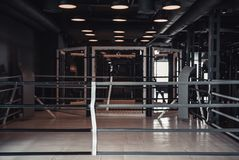 Modern boxing ring. In the gym, lights on the ceiling are turned on royalty free stock photos