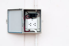 the modern breaker switch and white plug are hang on cement back Stock Image