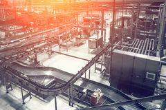 Modern brewery factory conveyor line and many steel pipes, toned as abstract industrial background stock photography