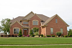 Modern Brick Home. Single family red brick home with lawn and sidewalk Royalty Free Stock Image