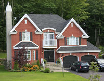Modern brick home with green grass in front. Canada Stock Images