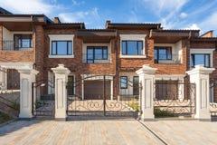 Modern brick house with plastic windows,  modern wrought-iron gates and chimney. Modern brick house with plastic windows,  modern wrought-iron gates and chimney Stock Photo