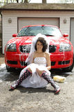 Modern bride portrait. Young bride sit in front of red car Stock Photos