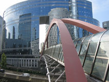 A modern bridge. A steel arch and a glass tunnel link two buildings in the La Defense district of Paris Royalty Free Stock Photography